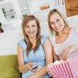 Two attractive female friends watching televison on the sofa eat — Stock Photo