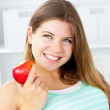 Smiling young woman holding an apple in her hand — Stock Photo