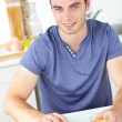 Charming young man using his laptop holding orange juice in the — Stock Photo