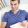 Laughing caucasian man eating popcorn on a sofa — Stock Photo #10832208