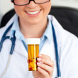 Glowing young female doctor holding pills — Stock Photo #10832250