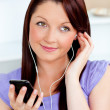 Attractive woman using her cellphone to listen to music with ear - Stock Photo