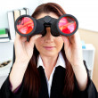 Young businesswoman looking through binoculars sitting at her de — Stock Photo