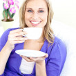 Merry young woman holding a cup of coffee on a sofa — Stock Photo