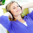 Relaxed caucasian woman listening to music with headphones lying — Stock Photo