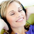 Charming caucasian woman listening to music with headphones lyin — Stock Photo