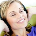 Charming caucasian woman listening to music with headphones lyin — Stock Photo