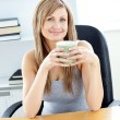 Stock Photo: Glowing businesswoman holding a cup at her desk