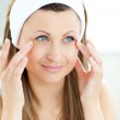 Cute young woman putting cream on her face in the bathroom — Stock Photo