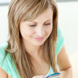 Happy young woman writing a message on her cellphone at home — Stock Photo #10832759