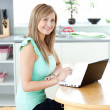 Delighted blond woman using her laptop smiling at the camera at — Stock Photo