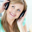 Delighted caucasian woman listening to music with headphones in - Stock Photo