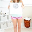 Smiling blonde woman holding a scale and looking at the camera i — Stock Photo #10832846