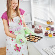 Cute young woman baking cookies in the kitchen — Stock Photo