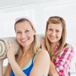 Stock Photo: Two cute women carrying carpet at home