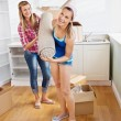 Stock Photo: Two positive women carrying carpet at home