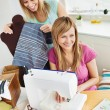 Happy young female friends sewing clothes together at home - ストック写真