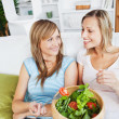 Two female friends eating salad together on a sofa - Stock Photo