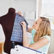 Delighted young woman sewing clothes at home — Stock Photo #10833064