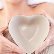 Close-up of a woman holding a bowl in the shape of a heart — Stock Photo
