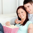 Affectionate couple lying on the sofa watching television in the — Stock Photo