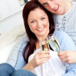 Loving couple drinking on a sofa — Stock Photo