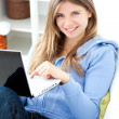 Positive woman using a laptop sitting on a sofa — Stockfoto