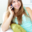 Positive woman talking on phone sitting on a sofa — 图库照片