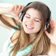 Delighted woman listening to music with headphones on a sofa — 图库照片 #10833428