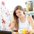 Enthusiastic young woman using her laptop while having breakfast — Stock Photo