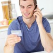Attractive young man talking on phone holding a card in the kitc — Stock Photo