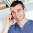 Happy young man talking on phone sitting on a sofa — Stock Photo