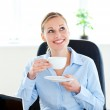 Delighted businesswoman drinking coffee in front of her laptop i — Stock Photo