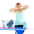 Unhappy woman ironing her clothes - Stock Photo