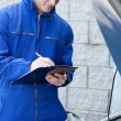 Handsome mechanic writing on a clipboard standing in front of a - Stock Photo
