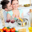 Bright couple preparing spaghetti in the kitchen and drinkng win — Stock Photo