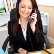 Concentrated businesswoman talking on phone and using her laptop — Stock Photo