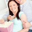 Royalty-Free Stock Photo: Hugging couple eating popcorn and watching television lying on t