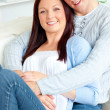 Royalty-Free Stock Photo: Portrait of a hugging couple sitting on a sofa in the living-roo