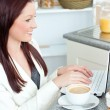 Positive businesswomusing her laptop during breakfast — Foto de stock #10834161