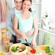 Stock Photo: Enamored young couple cutting vegetables in kitchen