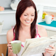Bright woman eating cereals while reading newspaper in the kitch — Stock Photo