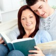 Stock Photo: Happy couple reading book in living-room lying on sofa