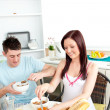 Young caucasian couple having breakfast together in the kitchen — Stock Photo