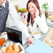 Couple of businesspeople having breakfast in the kitchen - Stock Photo