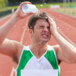 Young sprinter spraying water on his head — Stock Photo #10834368