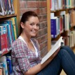 Stock Photo: Smiling young womreading book sitting on floor