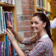 Stock Photo: Joyful young womlooking for book