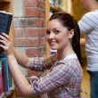 Stock Photo: Charming young womlooking for book