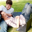 Couple of bright students using a laptop lying on the grass — Stock Photo #10834427